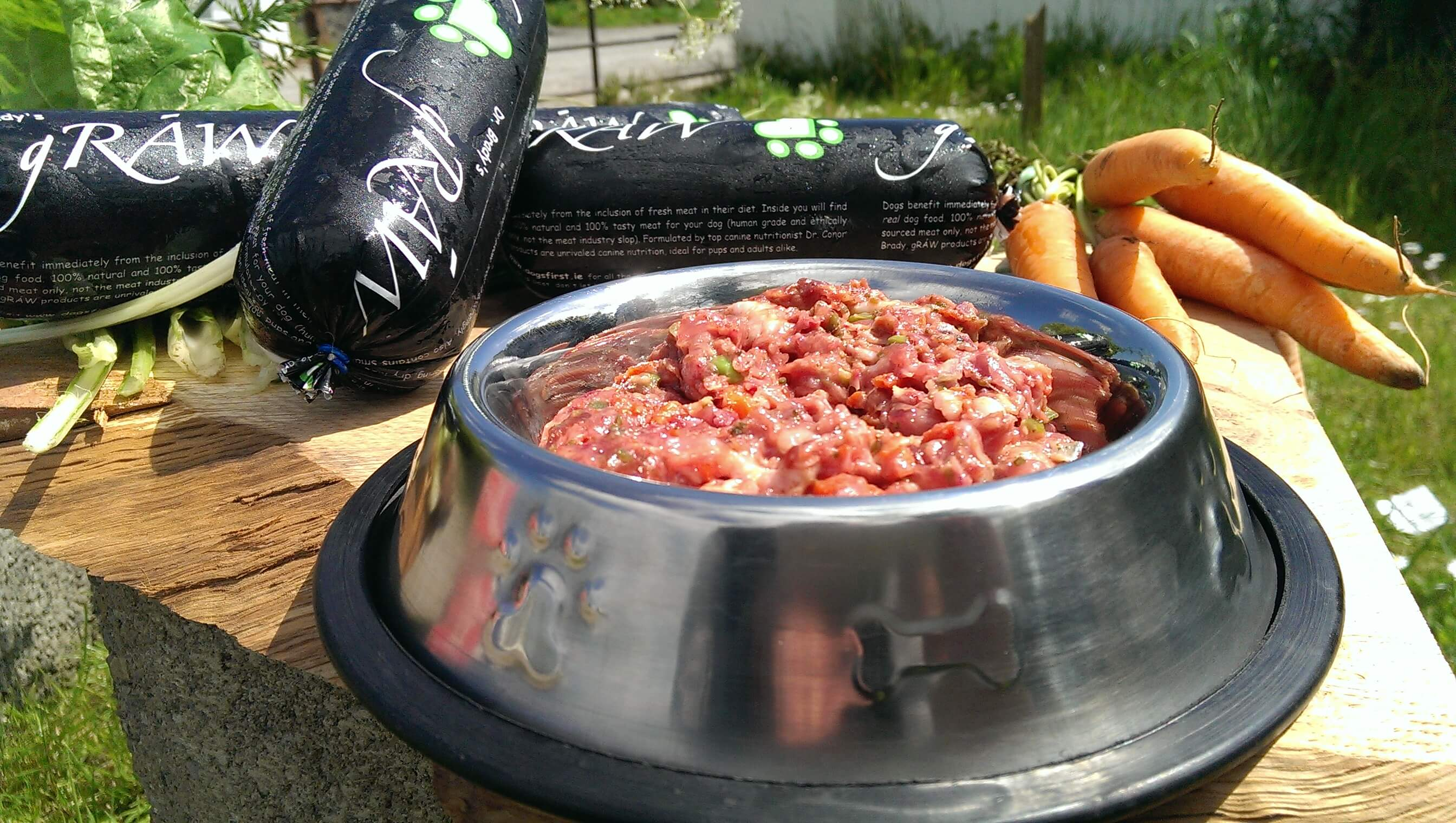 A bowl of raw dog food with some Graw Dog Food chubs beside it
