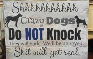 a sign that says don't knock on our door or our dogs will go mad and so will we!